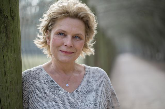 Die Schauspielerin Janette Rauch lehnt lächelnd an einem Baum