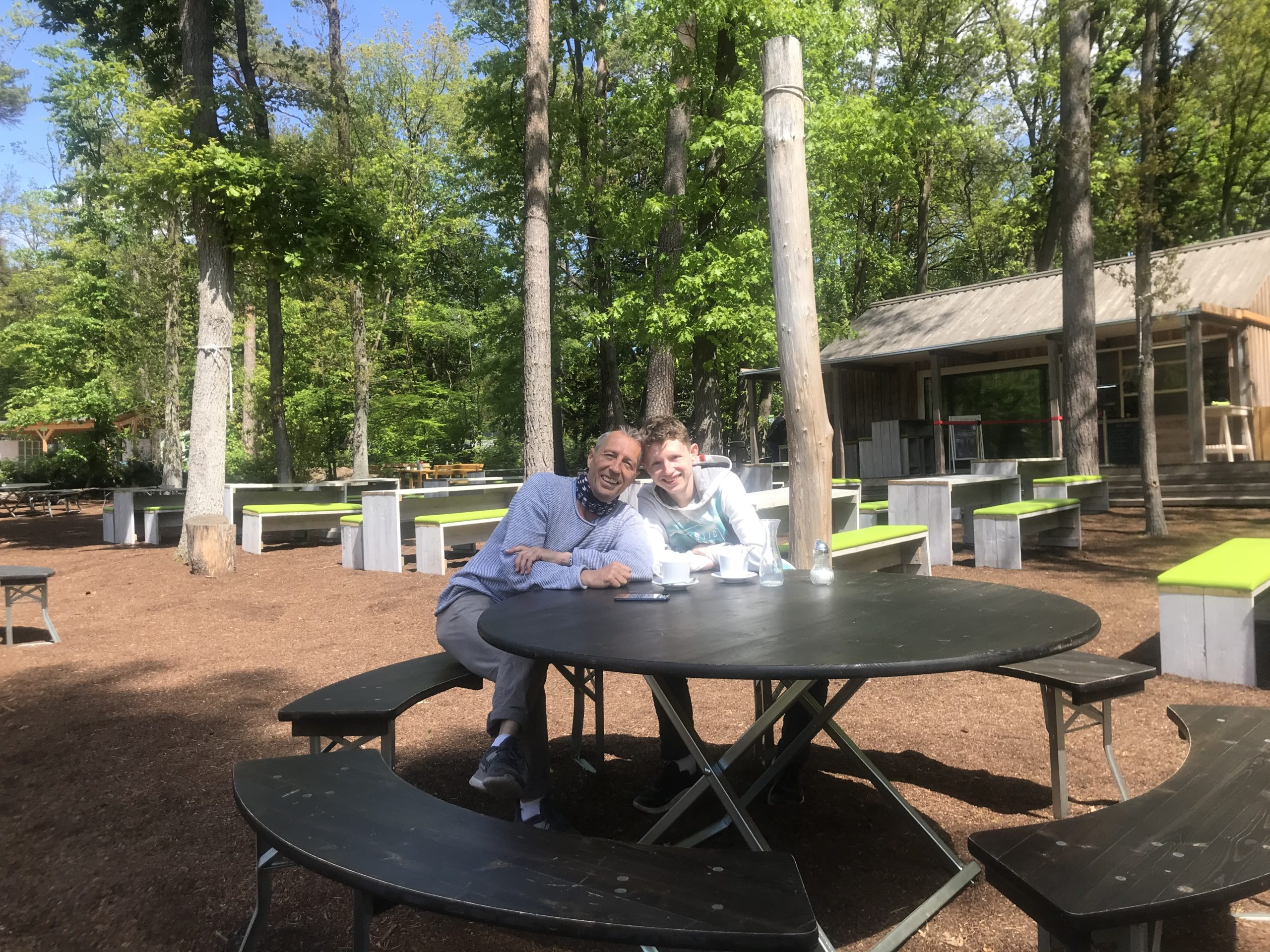 Vater und Sohn sitzen im Außen-Café des Barfußparks in Beelitz Heilstätten